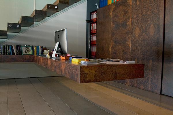 Biuro. Jeżeli potrzebujesz domowego biura zrób z przestrzeni pod schodami swoje miejsce pracy umieszczając w nim potrzebne książki, dokumenty, drukarkę itp. W takim miejscu możesz łatwiej się skupić i pracować w spokoju._przestrzeń pod schodami 52