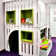 """Domek zabaw z """"sypialnią"""" na górze i małym schowkiem do zabawy w chowanego"""