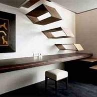 Ażurowe metalowe schody w formie skrzynek połączone ze stołem i miejscem do pracy w przestrzeni pod chodami. Pomysłowe i lekkie