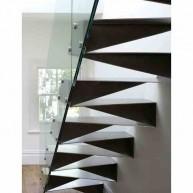 Ażurowe stalowe schody montowane w ścianie z barierką z tafli szkła montowaną do poszczególnych stopni.