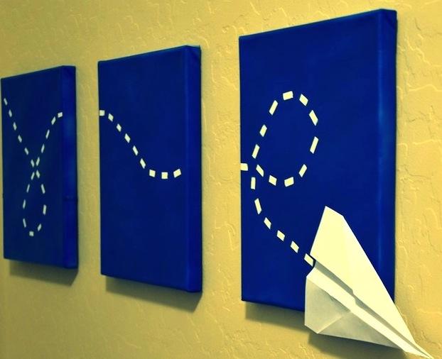 dekoracje-pokoju-dziecka-Blejtramy pomalowane na niebiesko z żółtym śladem statku z papieru - w sam raz na dekorację pokoju dla chłopca :)