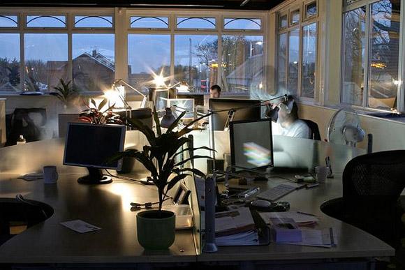 Strawberrysoup Office, Chichester. Mała przestrzeń z kilkoma stanowiskami pracy skupionymi wokół siebie. Ogromne okna pozwalają oderwać się na chwilę od pracy, a prosty design zapewnia miłą, przytulną atmosferę_nowoczesne_biuro_11