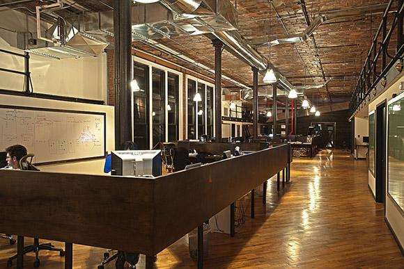 9mmedia Offices, Nowy York, USA. Biuro z paroma stanowiskami pracy utrzymane w ciepłej, brązowej kolorystyce z sufitem imitującym cegły i drewnianym parkietem - ciekawy projekt.