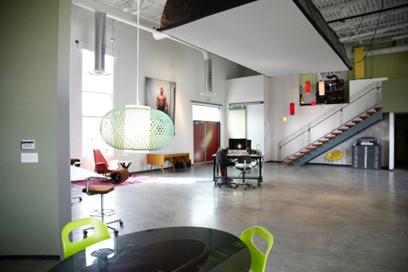 To samo biuro ze stanowiskami pracy wokół ścian oraz w centrum. Dużo otwartej przestrzeni i ciepłych barw relaksuje i wprowadza miłą atmosferę pracy_nowoczesne_biuro_4