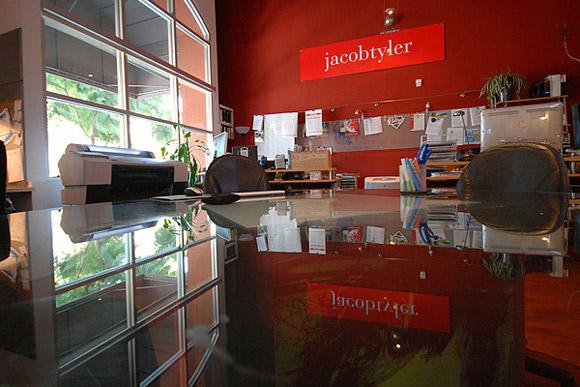 Jacob Tyler Creative Group, San Diego. Większe pomieszczenie z paroma stanowiskami pracy wyróżniają ogromne okna i czerwona ściana._nowoczesne_biuro_7