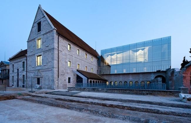 Zabytkowe, kamienne mury i nowoczesna szkoła ze szkła.
