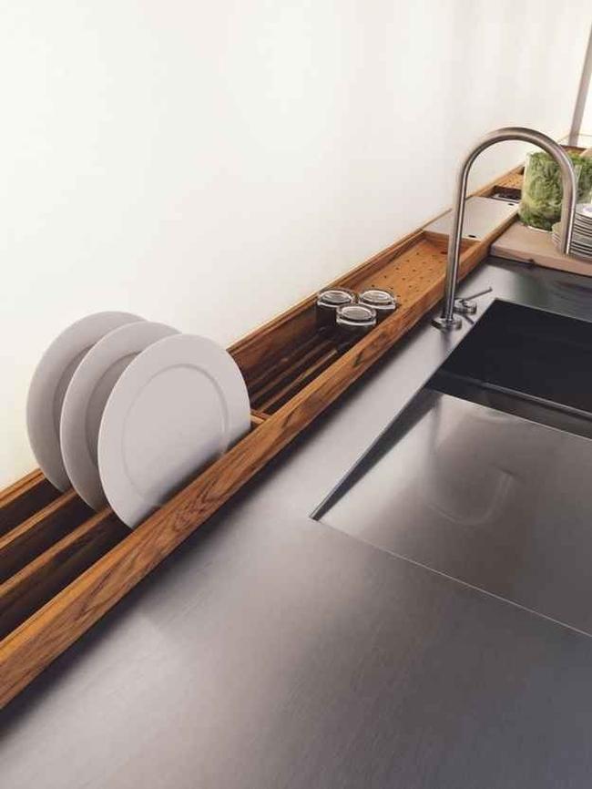 Ciekawy i designerski przykład na umieszczenie ociekarki na naczynia. Drewniany ociekacz zajmuje miejsce wzdłuż blatu, którego i tak nie wykorzystujesz.